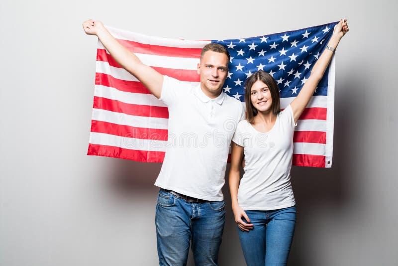 Portrait d'un jeune couple heureux sur le fond du drapeau des USA 4 juillet images stock