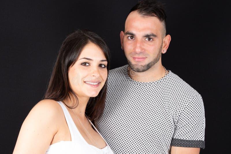 Portrait d'un jeune couple se tenant étroitement ensemble sur le fond noir photo stock