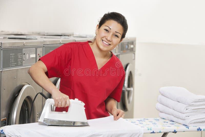 Portrait d'un jeune employé gai repassant dans la laverie automatique images libres de droits