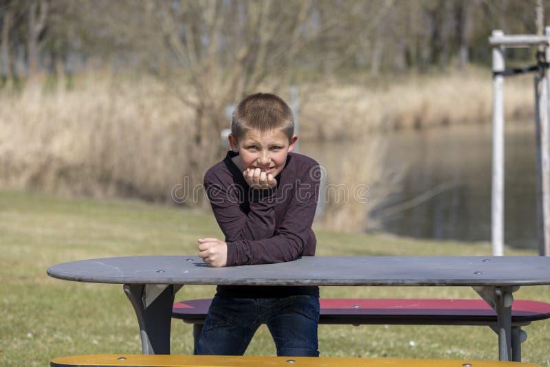 Portrait d'un jeune gar?on s'asseyant sur une table de pique-nique photos libres de droits