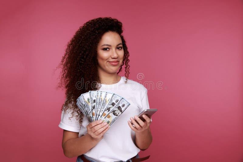 Portrait d'un jeune groupe africain enthousiaste de participation de femme de billets de banque et de regarder d'argent le téléph images stock
