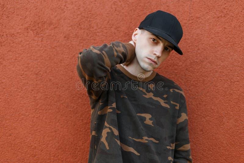 Portrait d'un jeune homme américain beau dans une chemise élégante de vert de camouflage dans un chapeau noir à la mode près d'un images libres de droits