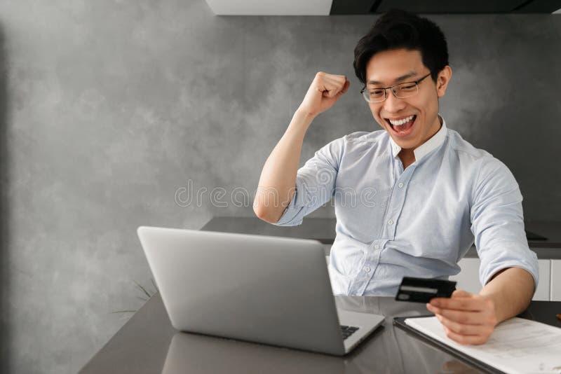 Portrait d'un jeune homme asiatique heureux tenant la carte de crédit photos stock