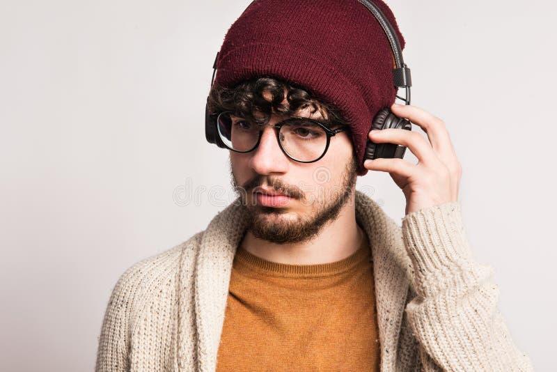 Portrait d'un jeune homme avec des écouteurs dans un studio photo stock