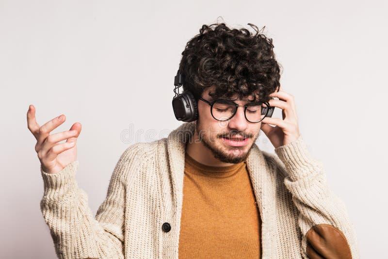 Portrait d'un jeune homme avec des écouteurs dans un studio images stock