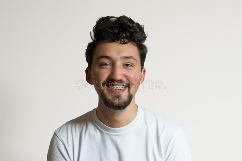 Portrait d'un jeune homme avec des accolades souriant et riant Un jeune homme heureux avec des accolades sur un fond blanc image stock
