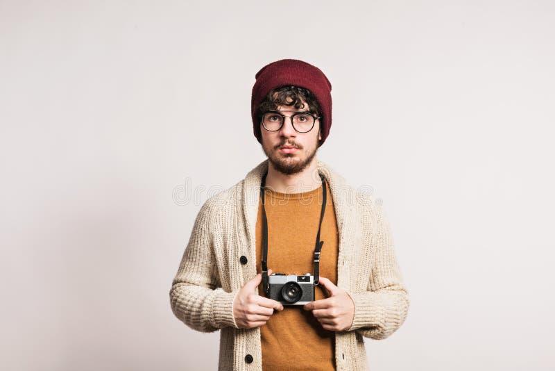 Portrait d'un jeune homme avec l'appareil-photo dans un studio photographie stock libre de droits