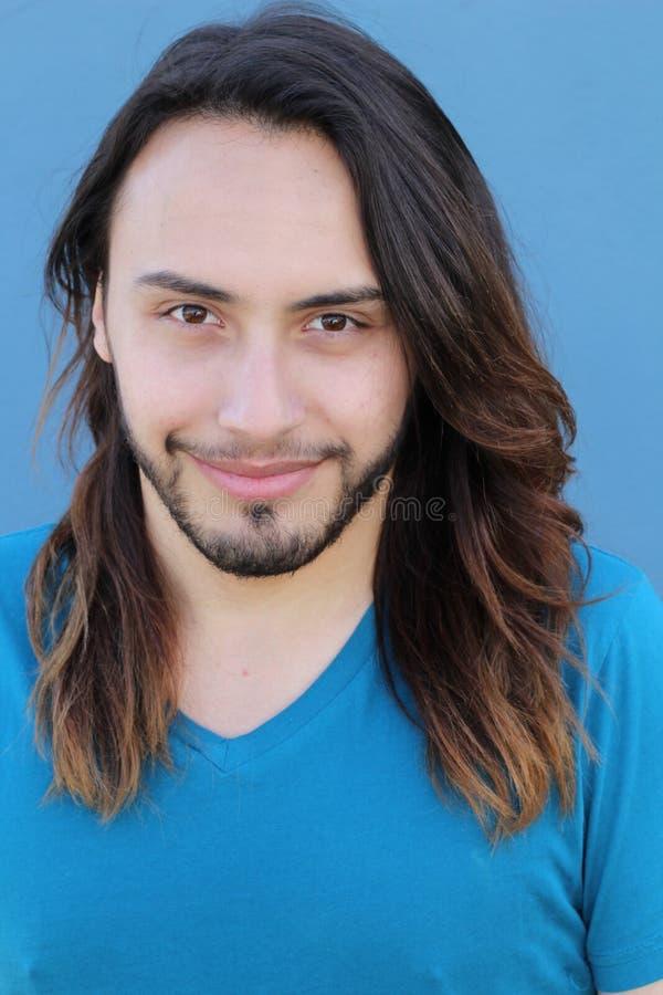 Portrait d'un jeune homme avec la longue coiffure fraîche regardant l'appareil-photo D'isolement sur le fond bleu images libres de droits
