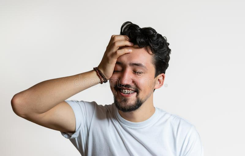 Portrait d'un jeune homme avec le sourire d'accolades Un jeune homme heureux avec des accolades sur un fond blanc photographie stock libre de droits