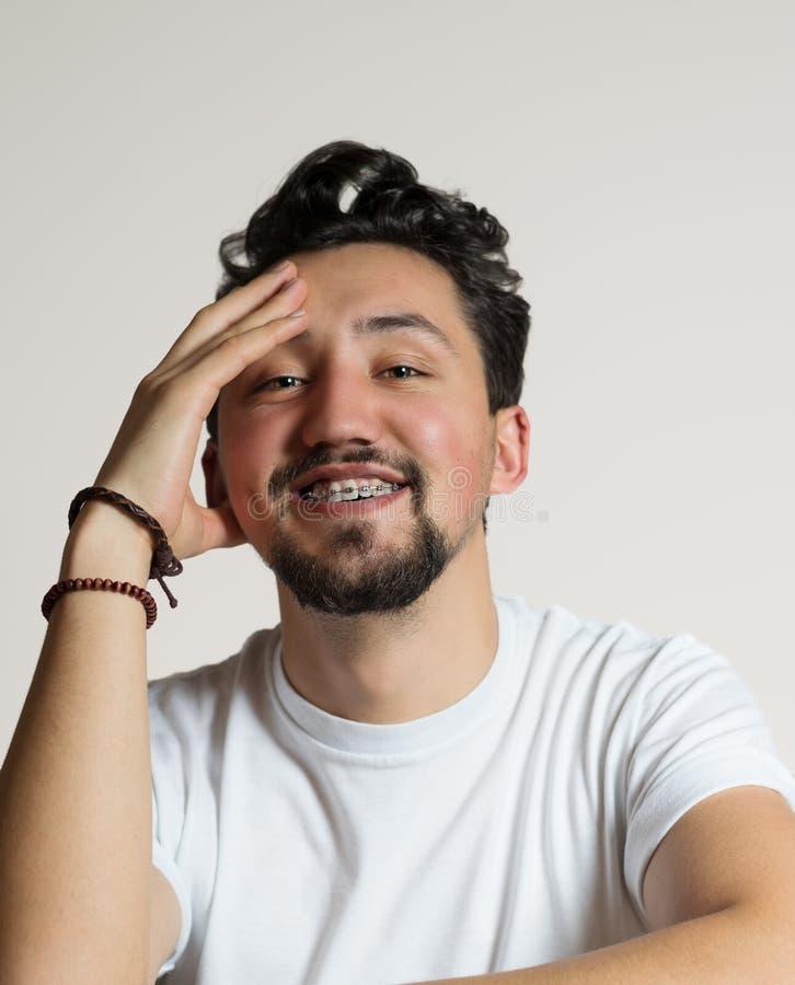 Portrait d'un jeune homme avec le sourire d'accolades Un jeune homme heureux avec des accolades sur un fond blanc images stock