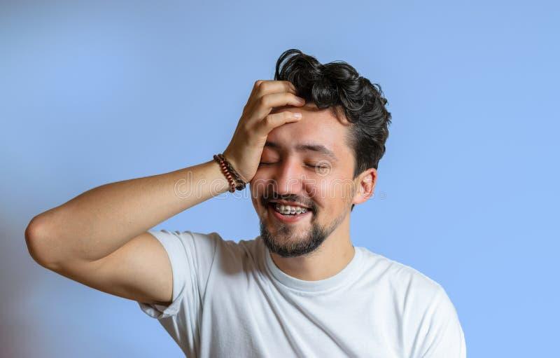 Portrait d'un jeune homme avec le sourire d'accolades Un jeune homme heureux avec des accolades sur un fond bleu photos stock