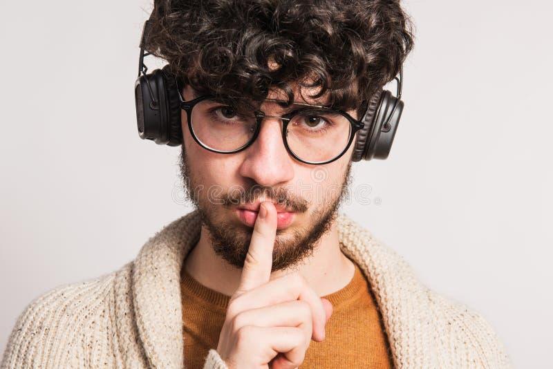 Portrait d'un jeune homme avec les écouteurs dans un studio, doigt sur sa bouche images libres de droits