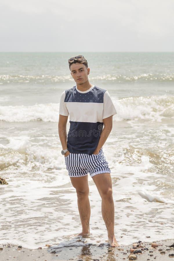Portrait d'un jeune homme avec ses mains dans des ses poches en mer photo stock