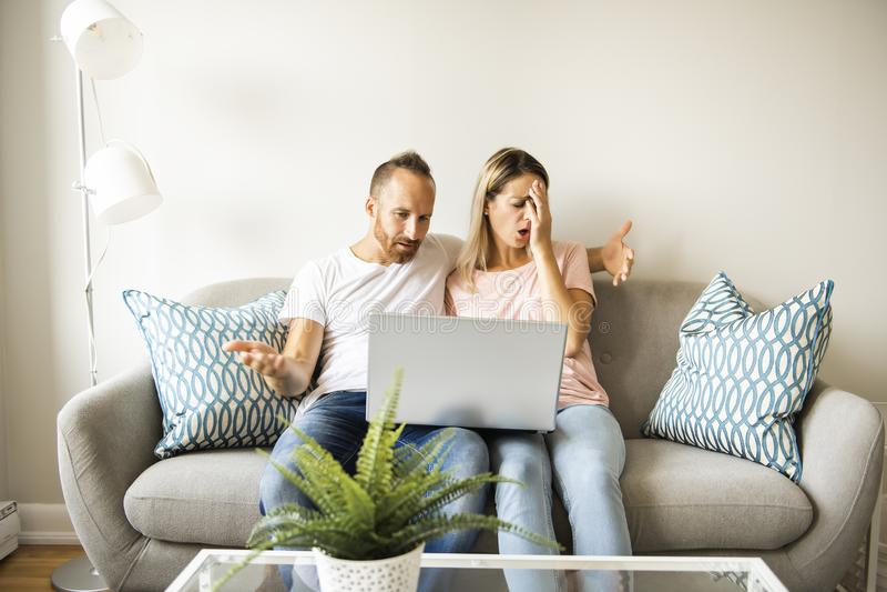 Portrait d'un jeune homme avec son amie sur l'ordinateur portable à la maison d'intérieur photo libre de droits