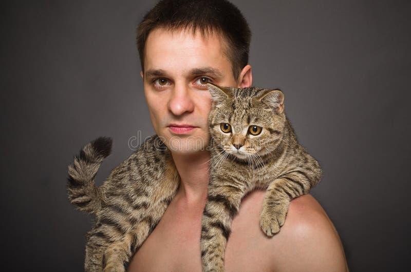 Portrait d'un jeune homme avec un chat images stock