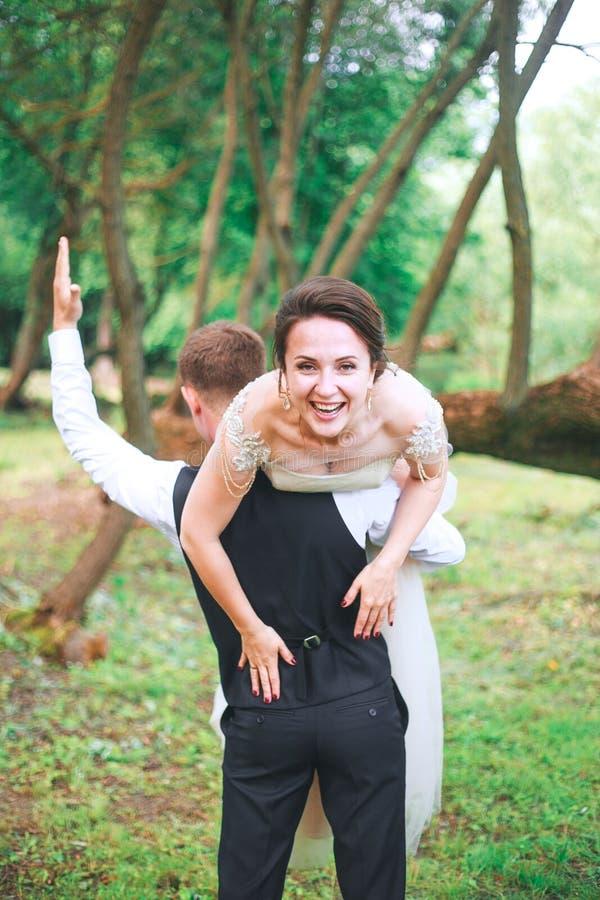 Portrait d'un jeune homme beau portant la femme attirante sur le sien dos dehors Couples d'amusement Jeune mariée et le GR photo stock