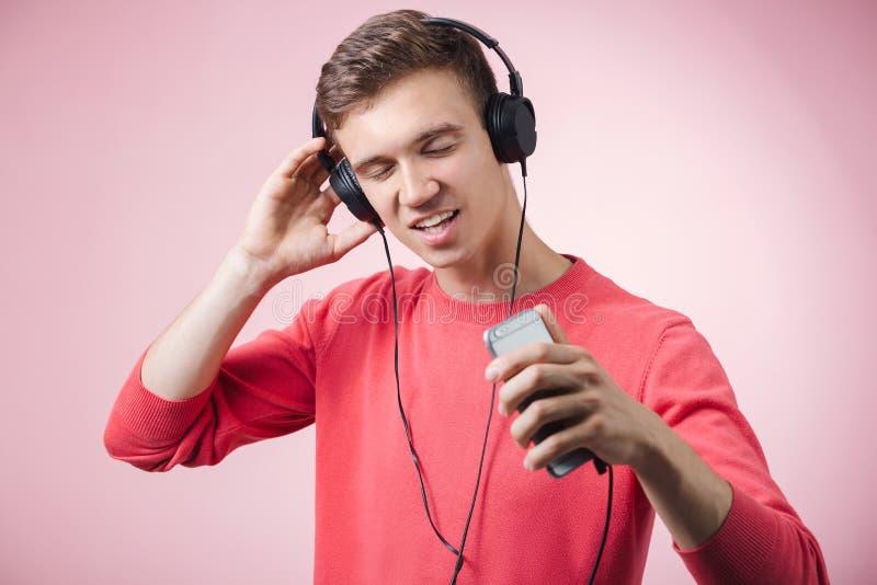 Portrait d'un jeune homme bel avec des écouteurs souriant et écoutant une musique avec un smartphone photos libres de droits