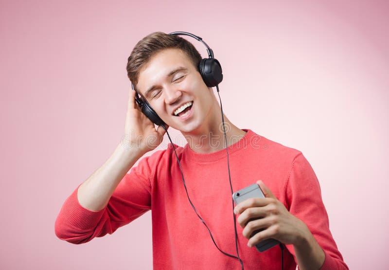 Portrait d'un jeune homme bel avec des écouteurs souriant et écoutant une musique avec un smartphone image stock