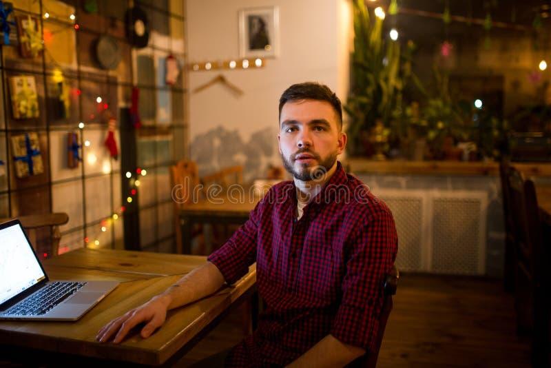 Portrait d'un jeune homme caucasien bel avec une barbe et de sourire toothy dans une chemise à carreaux rouge se reposant près d' photos stock