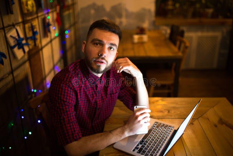 Portrait d'un jeune homme caucasien bel avec une barbe et de sourire toothy dans une chemise à carreaux rouge se reposant près d' images stock