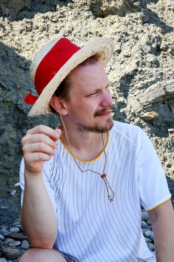 Portrait d'un jeune homme dans un chapeau de paille photos stock