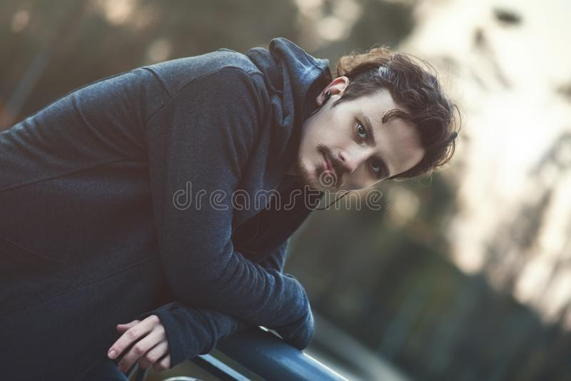 Portrait d'un jeune homme dans des ?couteurs promenade ? ?galiser le parc de ressort images stock