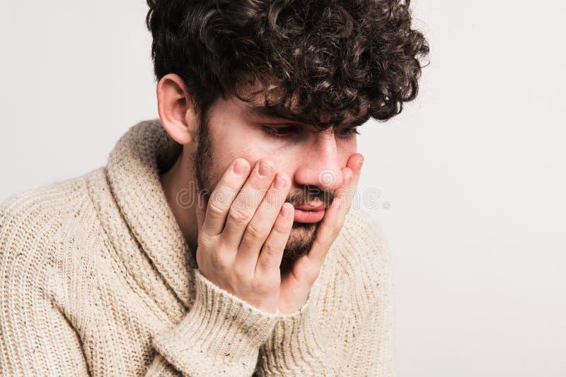 Portrait d'un jeune homme dans le cardigan de laine dans un studio photo libre de droits
