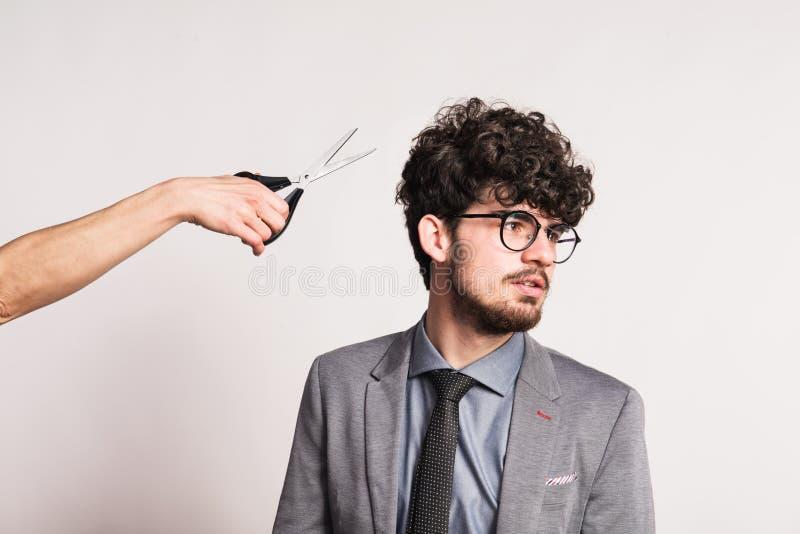 Portrait d'un jeune homme dans un studio et d'une main avec des ciseaux images stock