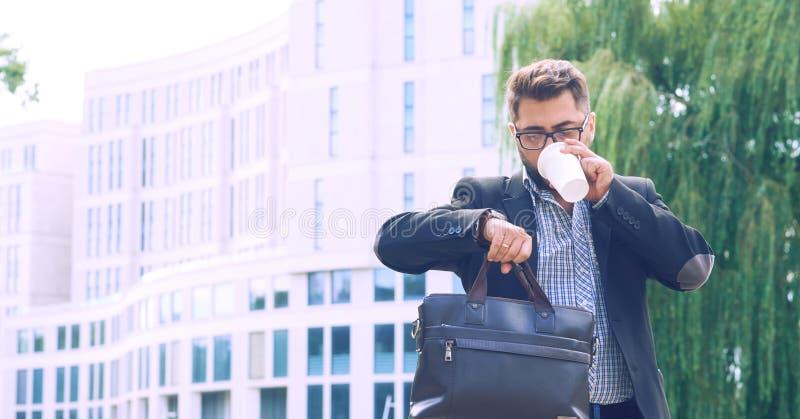 Portrait d'un jeune homme dans une veste avec une barbe et des verres descendant le café potable de rue et regardant photo libre de droits