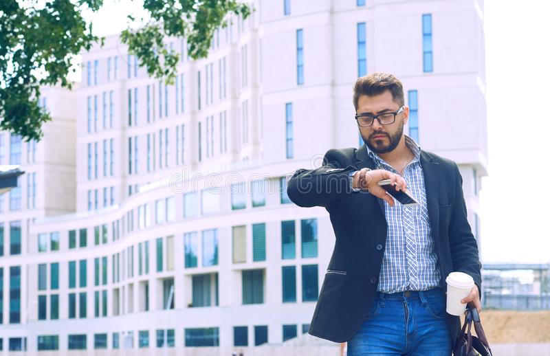 Portrait d'un jeune homme dans une veste avec une barbe et des verres descendant le café potable de rue et regardant images libres de droits