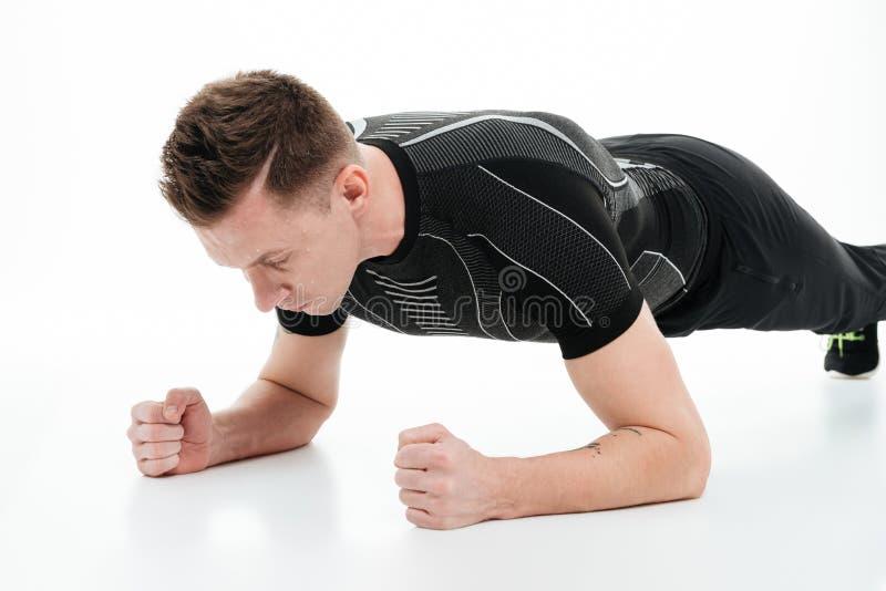 Portrait d'un jeune homme de forme physique faisant l'exercice de planche images stock