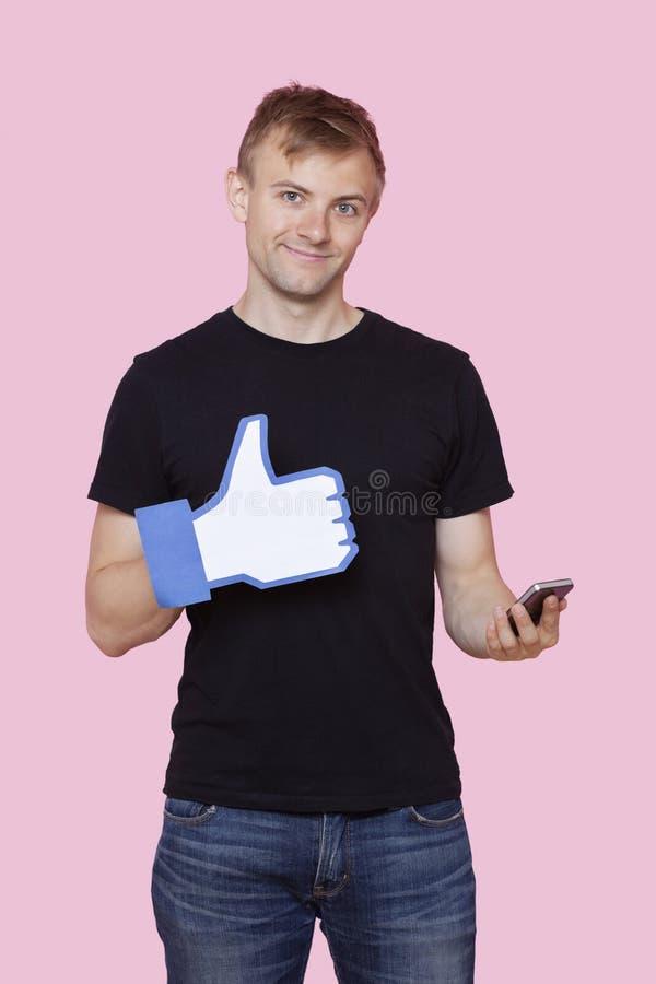 Portrait d'un jeune homme heureux avec le téléphone portable jugeant faux comme le bouton au-dessus du fond rose image stock
