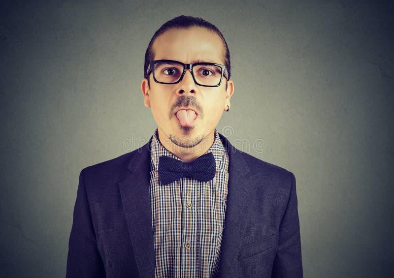 Portrait d'un jeune homme montrant sa langue images stock