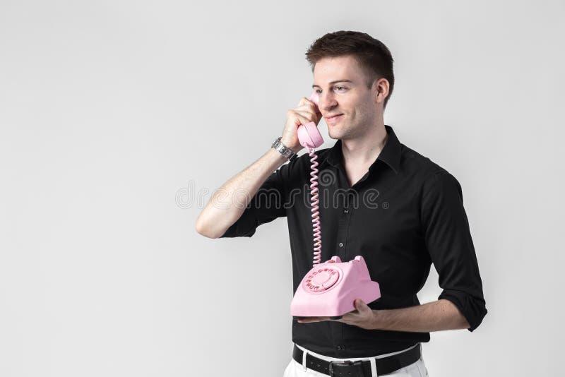 Portrait d'un jeune homme parlant à un téléphone de vintage au-dessus d'un wh photos libres de droits