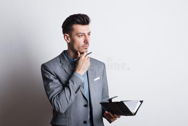 Portrait d'un jeune homme réfléchi avec un stylo et d'un journal intime dans un studio, prévoyant image libre de droits
