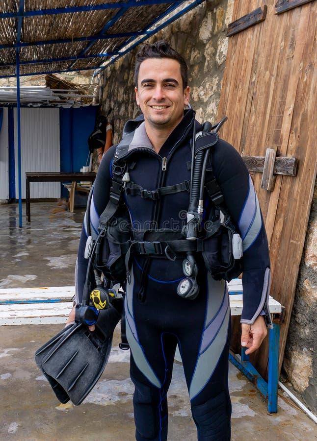 Portrait d'un jeune plongeur beau d'homme prêt à aller plongée à l'air avec le vêtement isothermique d'eau froide, ailerons, comp images stock