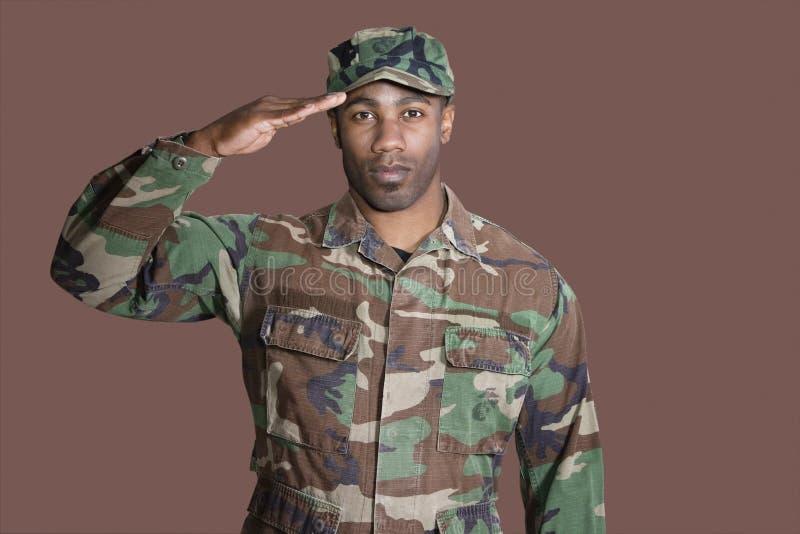 Portrait d'un jeune soldat des USA Marine Corps d'Afro-américain saluant au-dessus du fond brun photo libre de droits