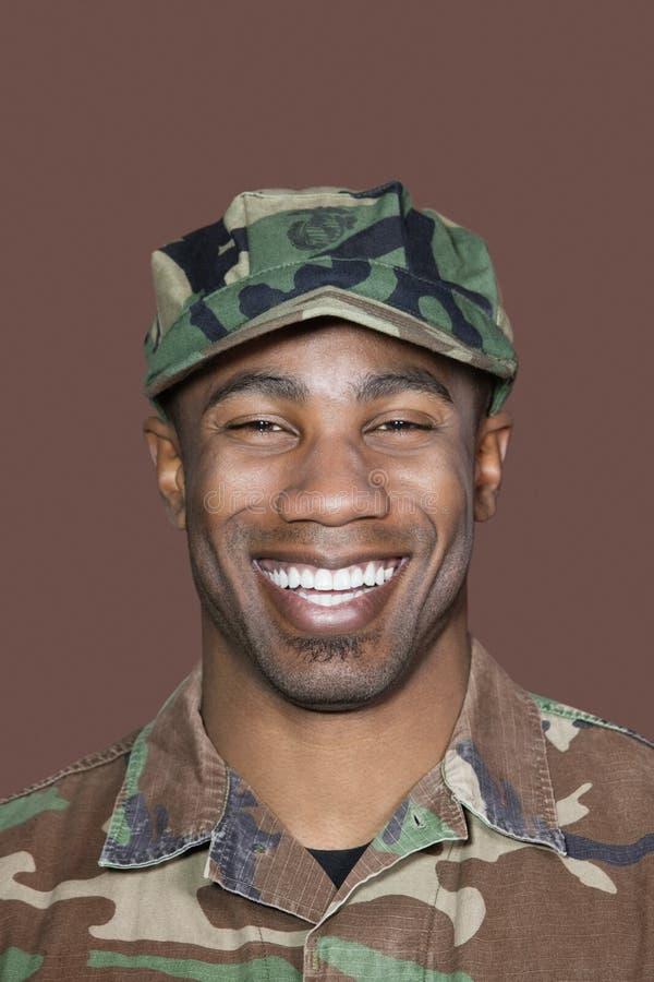Portrait d'un jeune soldat gai des USA Marine Corps d'Afro-américain au-dessus de fond brun photo libre de droits