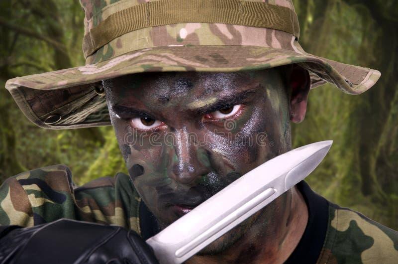 Portrait d'un jeune soldat peint avec le camouflage de jungle photo libre de droits