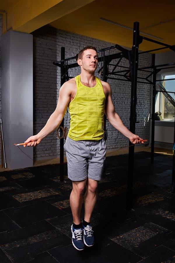 Portrait d'un jeune sportif dans le sportwear sautant avec une corde à sauter contre le mur de briques dans le gymnase photographie stock libre de droits