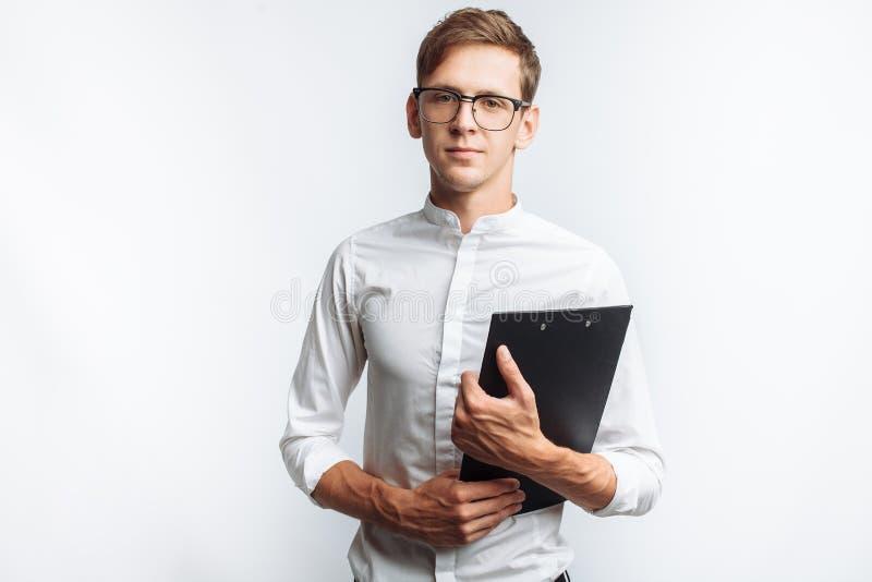 Portrait d'un jeune type attirant en verres, dans une chemise blanche, avec un dossier dans des ses mains, d'isolement sur un fon photographie stock