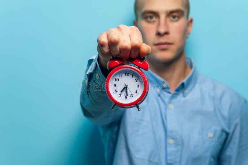 Portrait d'un jeune type beau dans la chemise bleue posant avec l'horloge rouge photos libres de droits
