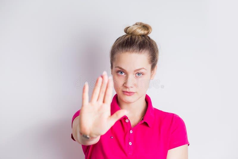 Portrait d'un jeune womanin sérieux dans la position rose de robe avec le geste tendu d'arrêt d'apparence de main au-dessus du fo photo libre de droits