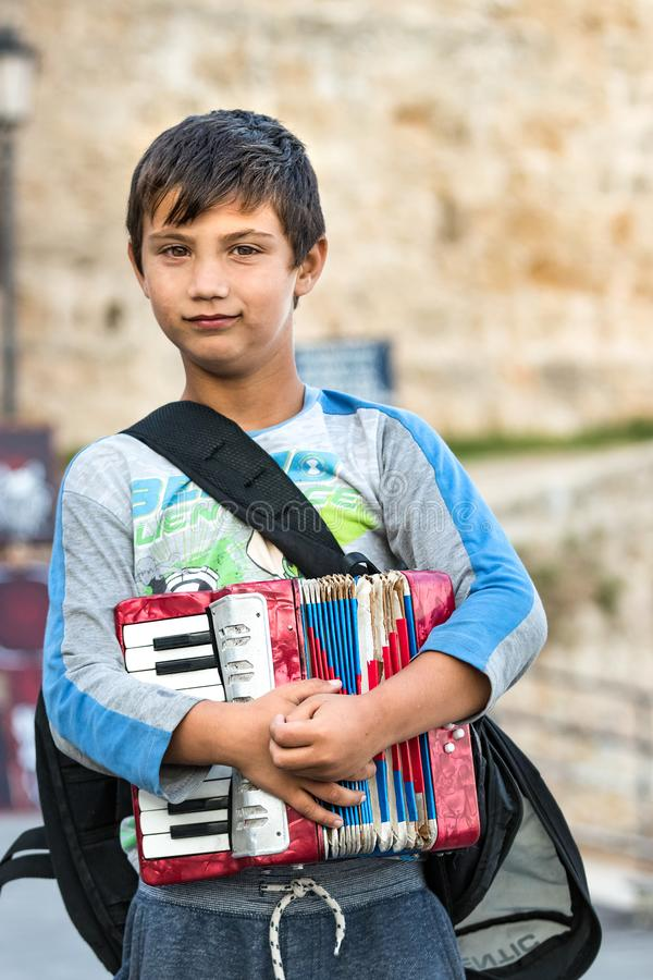 Portrait d'un joueur d'accordéon de garçon tenant son accordéon se tenant dehors au bord de mer de Rhodes, Grèce images stock