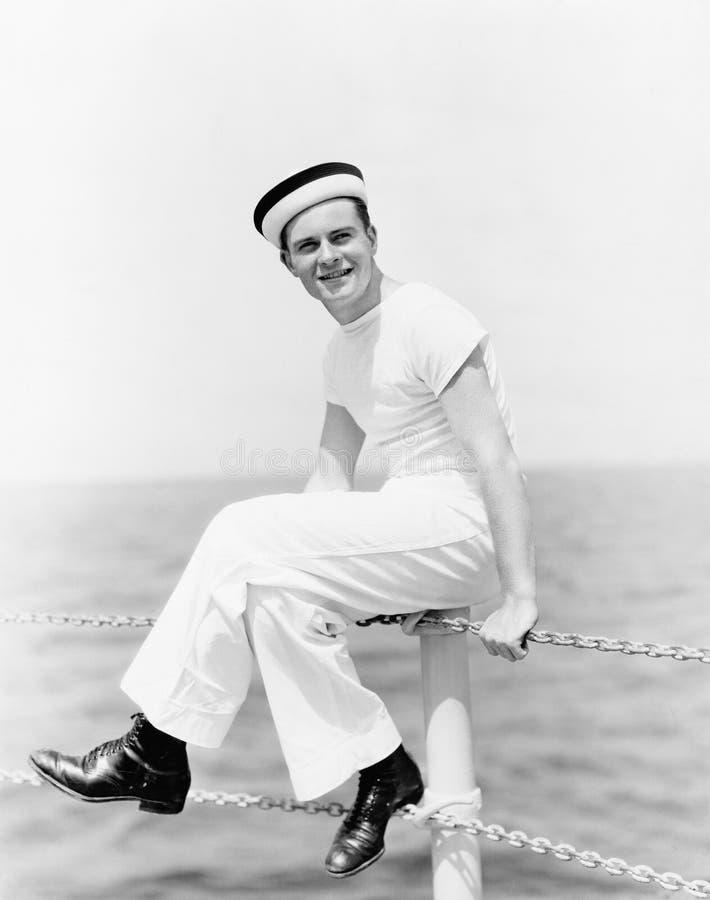 Portrait d'un marin s'asseyant sur le poteau d'un bateau et sourire (toutes les personnes représentées ne sont pas plus long viva image libre de droits