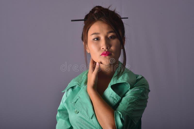 Portrait d'un modèle dans le manteau vert clair Kanzashi Fond gris photos libres de droits