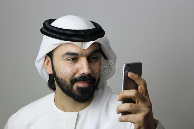 Portrait d'un mod?le masculin arabe Using Mobile And portant le MOBILE MOD?LE ARABE d'AFFAIRES de robe traditionnelle des EAU Emi photographie stock libre de droits