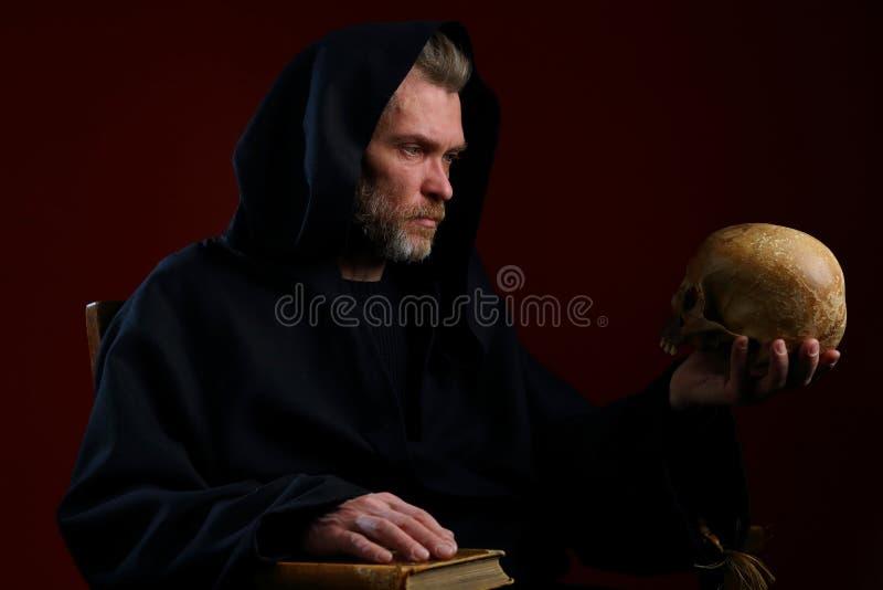 Portrait d'un moine médiéval avec un crâne dans des ses mains photographie stock libre de droits