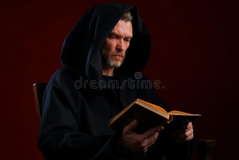 Portrait d'un moine médiéval avec un livre sur un fond de Bourgogne image stock