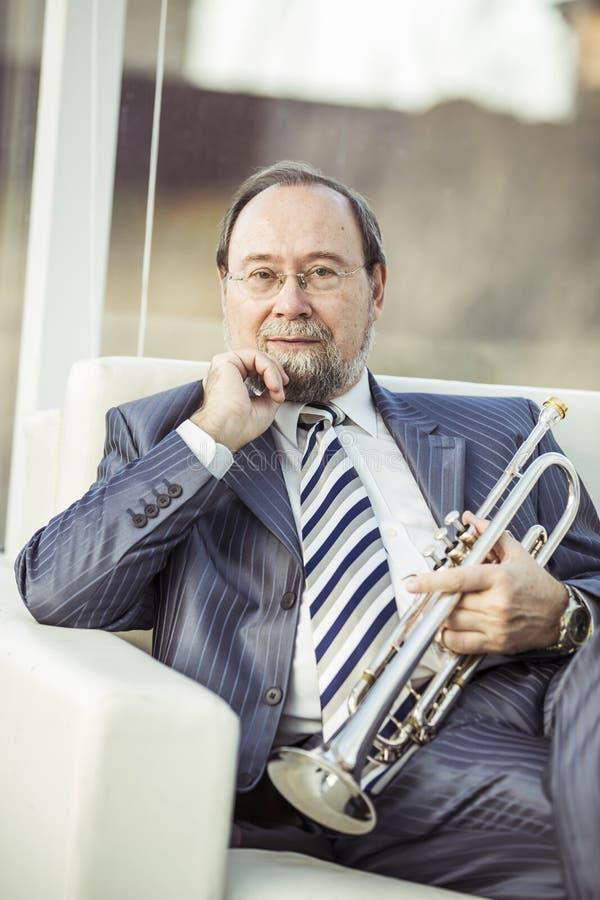 Portrait d'un musicien avec une trompette se reposant dans une chaise, sur le fond de la salle de concert photographie stock